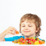 Smiling child with colored jelly candies on white background Royalty Free Stock Images