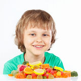 Smiling child with colored sweets and jelly candies on white background Stock Image