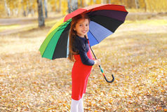 Smiling child with colorful umbrella walking in autumn Stock Photo