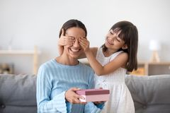 Smiling child daughter closing mom eyes congratulating with moth. Smiling child daughter closing eyes of excited mom holding pink gift box congratulating mum stock photos