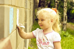 Smiling child drawing with chalk on the wall Stock Image