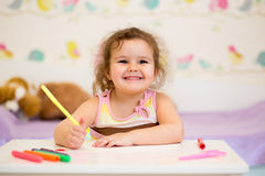 Smiling child drawing with felt-tip pen. Child girl drawing at table royalty free stock photos