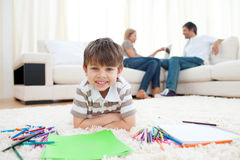 Smiling child drawing lying on the floor Royalty Free Stock Photos