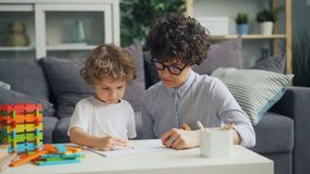 Smiling child is drawing with pencils while loving mother is talking helping