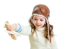Smiling child dressed pilot and playing with wooden airplane toy Stock Images