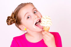 Smiling child eaiting ice-cream. A head portrait of a beautiful smiling caucasian girl child eaiting a delicious white vanilla ice-cream Stock Photos