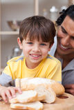 Smiling child eating bread with his father Royalty Free Stock Image