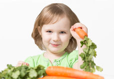 Smiling child eating a carrot. Healthy Eating Royalty Free Stock Photos