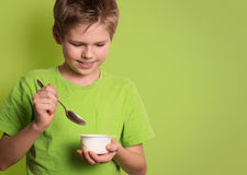 Smiling child eating yogurt  on green background with co. Py-space Royalty Free Stock Image
