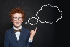 Smiling child and empty speech clouds bubbles on chalkboard background royalty free stock images