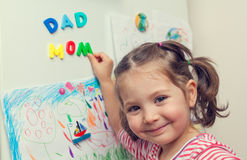 Smiling child forms mom dad words on refrigerator. Closeup photograph of smiling child hand forming mom and dad words with magnetic letters on refrigerator door stock image