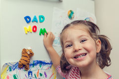 Smiling child forms mom dad words on refrigerator Stock Image