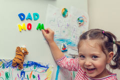 Smiling child forms mom dad words on refrigerator Royalty Free Stock Photos