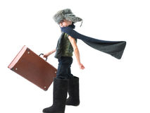 Smiling child in a fur hat and felt boots purposefully moving forward with developing scarf and holds old suitcase in his hand Royalty Free Stock Image