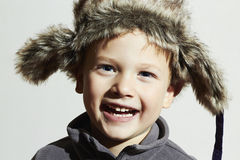 Smiling child in fur Hat.Kids casual winter style.fashion little funny boy.children emotion. Hat ear flaps Stock Image