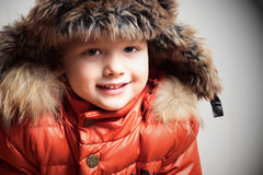Smiling child in fur hood and orange winter jacket.fashion boy Royalty Free Stock Image