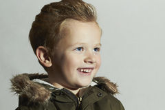 Smiling child.fur hood and winter jacket. fashion kids.children.happy little boy winter style Royalty Free Stock Photos