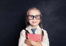 Smiling Child Girl with Book on Blackboard. Background with Copy space. Small Girl in Glasses. Back to School Concept royalty free stock photos