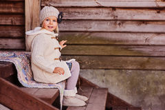 Smiling child girl at country house sitting on stairs Royalty Free Stock Photos