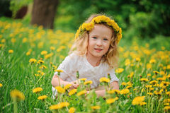 Smiling child girl in dandelion wreath on spring flower field Stock Photo