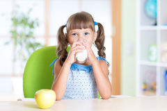 Smiling child girl drinking milk from glass at Royalty Free Stock Photography