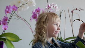 Smiling child girl face near purple and white orchids. stock video