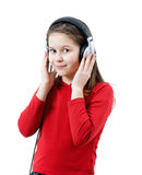 A smiling child girl listens to music through headphones Royalty Free Stock Photo