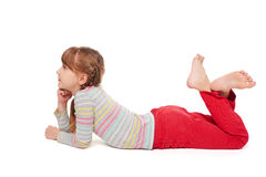 Smiling child girl lying on stomach on the floor. Side view of smiling child girl lying on stomach on the floor with crossed legs looking forward, over white royalty free stock images