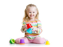 Smiling child girl playing with color toys Stock Images