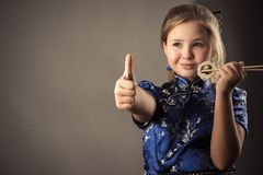 Smiling child girl with roll in hand shows gesture thumb up royalty free stock photo