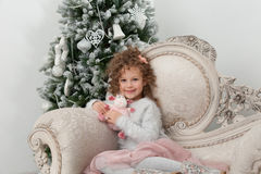 Smiling child girl with sheep toy and Christmas tree Royalty Free Stock Images