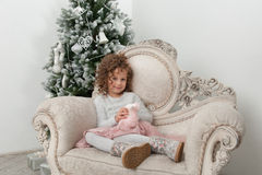 Smiling child girl with sheep toy near Christmas tree Stock Photography