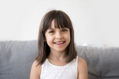 Smiling child girl talking to camera making video call vlog. Adorable cute little vlogger looking at webcam, smiling child girl talking to camera making video stock photo