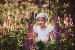 Smiling child girl in white shirt and headband playing on summer lupin field Royalty Free Stock Photo