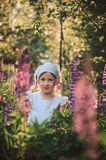 Smiling child girl in white shirt and headband playing on summer lupin field Stock Photos