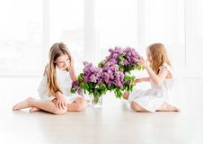Smiling child girls with lilac bouquet Stock Image