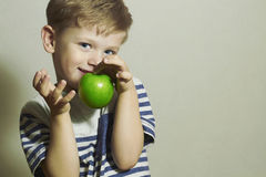 Smiling Child with Green apple.Little Handsome Boy.Health.Fruits Royalty Free Stock Photography