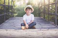 Smiling child. Happy boy sitting in the field with hat Stock Photography