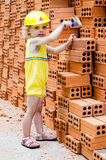 Smiling child with hard hat at orange bricks background Stock Photography