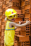 Smiling child with hard hat at orange bricks background Stock Photos