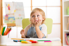 Smiling child having an idea while drawing in nursery room. Smiling child having an idea while drawing royalty free stock image