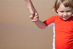 Smiling child holding hand of woman at beach Royalty Free Stock Photos