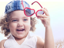 Smiling child with holding red sun glasses Royalty Free Stock Photography