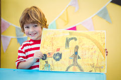 Free Smiling Child Holding Up His Finished Painting Royalty Free Stock Photos - 62322248