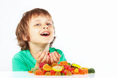 Smiling child with jelly candies on white background Royalty Free Stock Photo