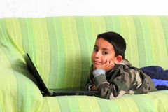 Smiling child with laptop. Smiling child over the sofa with a laptop Royalty Free Stock Images
