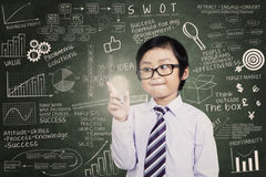 Smiling child with a lit bulb. Smiling asian child with a lit bulb at classroom Stock Photo