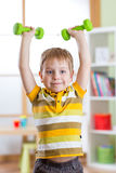 Smiling child little boy exercising with dumbbells. Healthy life and sport concept. Royalty Free Stock Photos