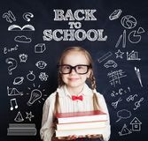 Smiling child little girl in class room with blue chalkboard. Back to school royalty free stock images
