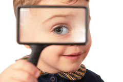 Smiling child looks through magnifier Stock Images